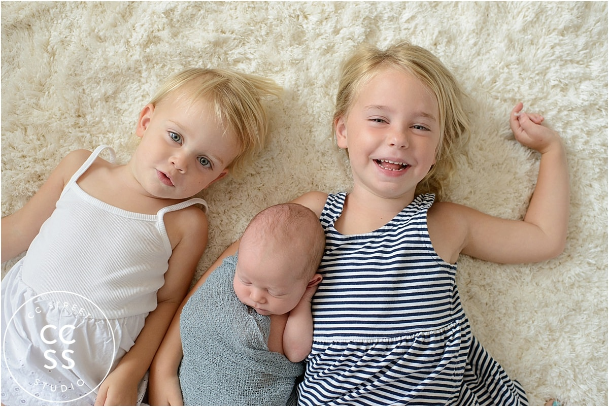 newborn baby with sisters photo